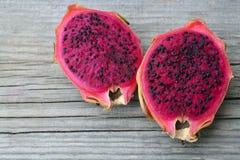 异乎寻常的成熟桃红色Pitaya或龙果子 红色Pitahaya热带水果在老木桌上切成了两半 库存照片