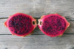 异乎寻常的成熟桃红色Pitaya或龙果子 红色Pitahaya热带水果在老木桌上切成了两半 图库摄影