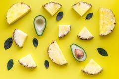 异乎寻常的果子样式 Pinneapple和鳄梨片在黄色背景顶视图 免版税图库摄影