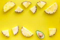 异乎寻常的果子样式 Pinneapple和鳄梨片在黄色背景顶视图copyspace 免版税库存照片