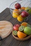 异乎寻常的果子特写镜头的分类:猕猴桃、红色和绿色苹果、桔子和柠檬在木桌上 免版税图库摄影