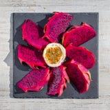 异乎寻常的桃红色龙果子裁减和passionfruit在背景关闭 甜热带水果、水多的pitaya和西番莲果裁减 免版税库存照片