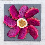 异乎寻常的桃红色龙果子裁减和passionfruit在背景关闭 甜热带水果、水多的pitaya和西番莲果裁减 免版税库存图片