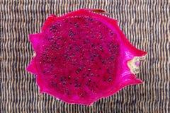 异乎寻常的桃红色dragonfruit切开了在背景的宏观照片 龙果子关闭 Pitahaya纹理照片 甜热带水果,水多 免版税库存图片