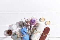 异乎寻常的花按摩产品温泉向毛巾扔石头 腌制槽用食盐、干燥花淡紫色,肥皂、蜡烛和毛巾 在白色木背景,顶视图的平的位置 免版税库存照片