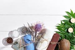 异乎寻常的花按摩产品温泉向毛巾扔石头 腌制槽用食盐、干燥花淡紫色,肥皂、蜡烛和毛巾 在白色木背景,顶视图的平的位置 库存图片