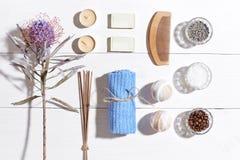 异乎寻常的花按摩产品温泉向毛巾扔石头 腌制槽用食盐、干燥花淡紫色,肥皂、蜡烛和毛巾 在白色木背景,顶视图的平的位置 图库摄影
