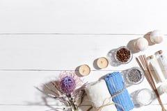 异乎寻常的花按摩产品温泉向毛巾扔石头 腌制槽用食盐、干燥花淡紫色,肥皂、蜡烛和毛巾 在白色木背景,顶视图的平的位置 库存照片