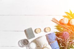 异乎寻常的花按摩产品温泉向毛巾扔石头 腌制槽用食盐、干燥花淡紫色,肥皂、蜡烛和毛巾 在白色木背景,顶视图的平的位置 免版税库存图片