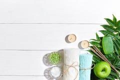 异乎寻常的花按摩产品温泉向毛巾扔石头 腌制槽用食盐、肥皂、蜡烛和毛巾 在白色木背景,顶视图的平的位置 库存照片