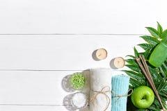 异乎寻常的花按摩产品温泉向毛巾扔石头 腌制槽用食盐、肥皂、蜡烛和毛巾 在白色木背景,顶视图的平的位置 免版税图库摄影