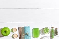 异乎寻常的花按摩产品温泉向毛巾扔石头 腌制槽用食盐、肥皂、蜡烛和毛巾 在白色木背景,顶视图的平的位置 免版税库存图片