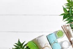 异乎寻常的花按摩产品温泉向毛巾扔石头 腌制槽用食盐、肥皂、蜡烛和毛巾 在白色木背景,顶视图的平的位置 库存图片