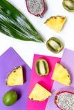 异乎寻常的果子片断  Dragonfruit、菠萝和猕猴桃在白色背景顶视图 免版税库存图片