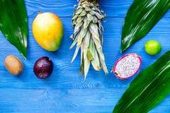 异乎寻常的果子膳食 Dragonfruit、山竹果树、芒果、猕猴桃、石灰和菠萝在蓝色木背景顶视图copyspace 免版税库存照片