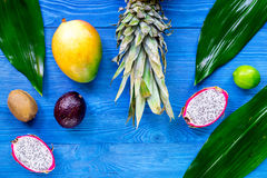 异乎寻常的果子膳食 Dragonfruit、山竹果树、芒果、猕猴桃、石灰和菠萝在蓝色木背景顶视图copyspace 库存图片