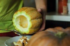异常的万圣夜瓜,削减过程、种子和残羹剩饭在厨房用桌、刀子和男性手上 库存图片