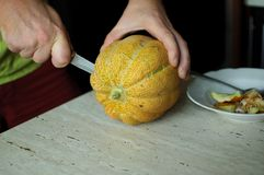 异常的万圣夜瓜,削减过程、种子和残羹剩饭在厨房用桌上 免版税库存图片