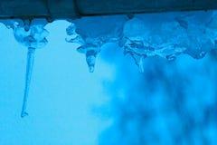 异常的形状卷曲蓝色冰柱在蓝色日落背景的 图库摄影