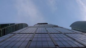 异常的形状现代蓝色摩天大楼,由玻璃制成 从下面在自转 影视素材