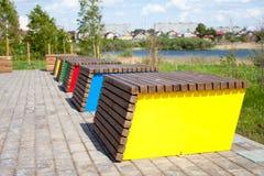 异常的装饰长木凳在河附近的城市公园 库存图片