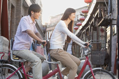 年轻异性爱夫妇侧视图在一辆纵排自行车的在北京 免版税库存照片