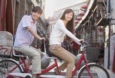 年轻异性爱夫妇侧视图在一辆纵排自行车的在看照相机的北京 库存图片