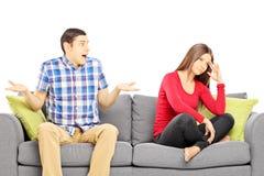 年轻异性爱夫妇坐沙发在论据期间 库存图片