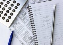 弄乱在您的桌面上 计算器,笔记本,文件 免版税库存照片