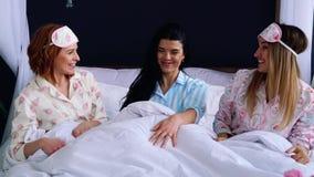 弄乱在睡衣的一条毯子下下床微笑和看彼此的三个女孩 影视素材