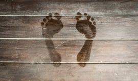 在黑暗的木板条地板上的湿脚印。 免版税库存图片