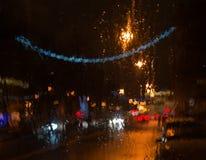 弄湿车窗有城市光背景  库存照片