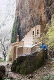 弄湿他的在瀑布的登山家手在偏僻寺院前面 库存照片