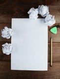 弄皱与白纸和一支铅笔板料的纸在棕色木背景 库存图片