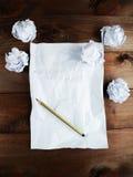 弄皱与白纸和一支铅笔板料的纸在棕色木背景 免版税库存照片