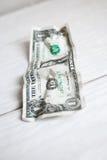 弄皱在白色木背景的一美元 库存图片