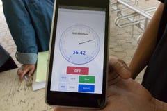 弄脏在手机的湿气app监测的湿气 相互 免版税库存图片