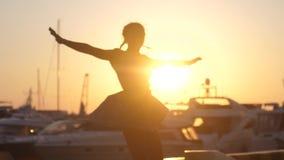 弄脏礼服的快乐的妇女转动跳舞在日落海船、游艇和透镜火光作用反对 股票视频