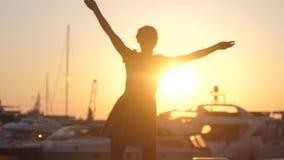 弄脏转动舞蹈的礼服的愉快的妇女,跳跃在日落海船、游艇和透镜火光作用 股票录像