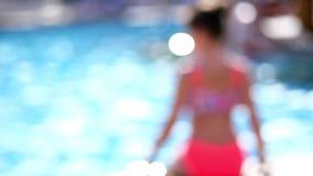 弄脏,在焦点外面 夏天,明亮的好日子,明亮的泳装的一个少年女孩在水池是休息,晒日光浴 股票视频