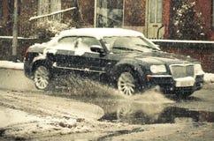 弄脏  黑汽车在大水坑乘坐在多雪的天 图库摄影