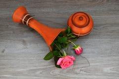 弄翻有玫瑰的花瓶 花瓶是一个木基地 水漏在花瓶外面 库存照片