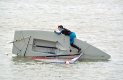 弄翻航行充气救生艇以年轻人尝试在费利克斯托萨福克英国纠正它,在海 库存图片