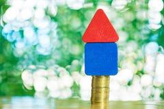 式样与步的房子木形式在桌上的硬币堆,真正的ES 免版税库存照片