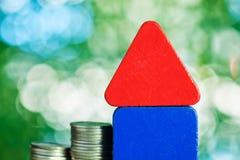 式样与步的房子木形式在桌上的硬币堆,真正的ES 免版税库存图片