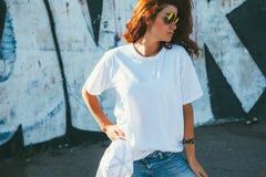 式样佩带的简单的摆在街道的T恤杉和太阳镜wal 免版税库存图片