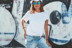 式样佩带的简单的摆在街道的T恤杉和太阳镜wal 库存照片
