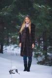 年轻式样女孩步行在冬天森林里 免版税库存图片