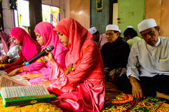 读仪式的孩子古兰经在古兰经的毕业。 免版税库存照片