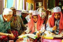 读仪式的孩子古兰经在古兰经的毕业。 库存图片